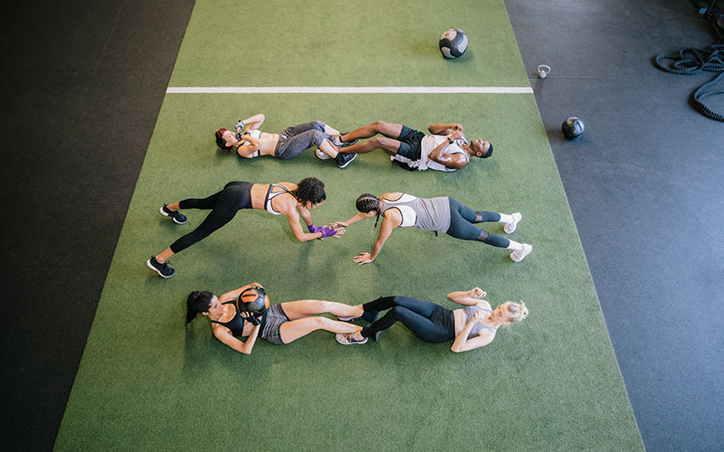 A group of white people and one person of color complete a workout as part of their weight loss workout plan