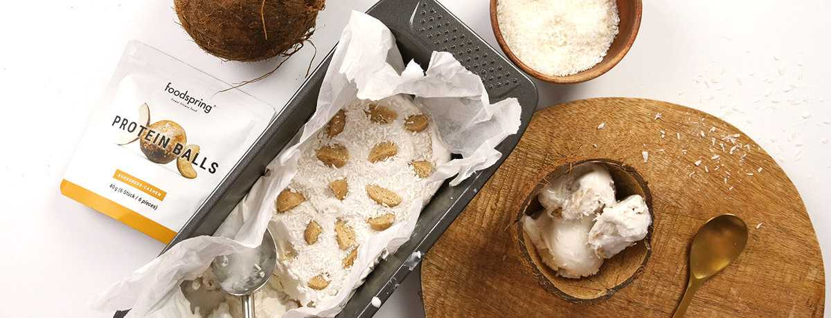 A container of coconut ice cream topped with quartered Protein Balls