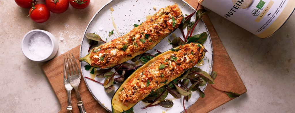 two halves of a stuffed zucchini filled with bright toppings