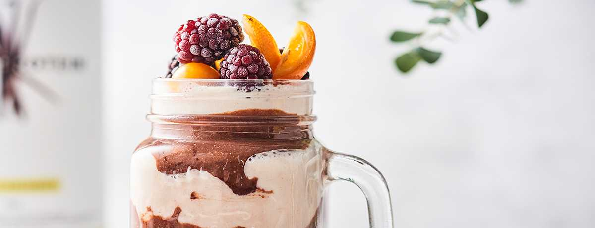 a vanilla chocolate shake in light and dark brown layers topped with fresh fruits and berries
