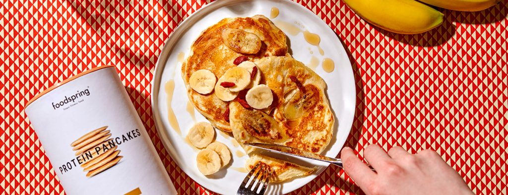 Two protein banana pancakes on a white plate sprinkled with banana slices and goji berries and drizzled artistically with dots of maple syrup.