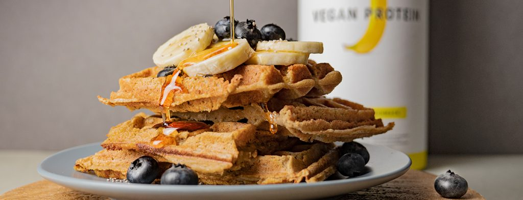 A stack of golden-brown, fluffy vegan banana waffles garnished with banana slices, blueberries, and maple syrup, with a canister of banana Vegan Protein behind it