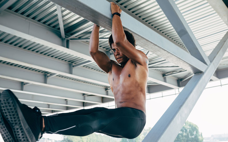 A shirtless man of color performs flexibility exercises while hanging from an outdoor ceiling
