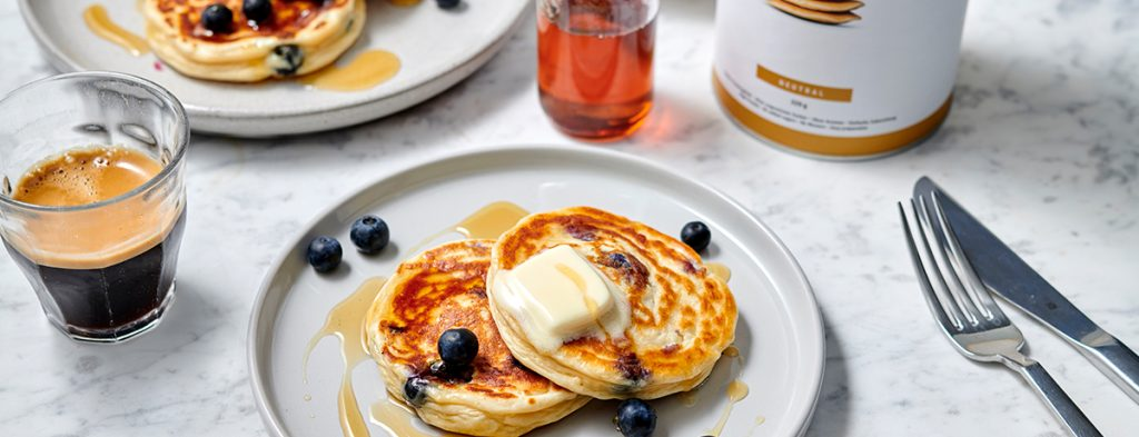 A stack of blueberry protein pancakes on a white plate, garnished with a square of margarine, a dollop of maple syrup, and fresh blueberries.