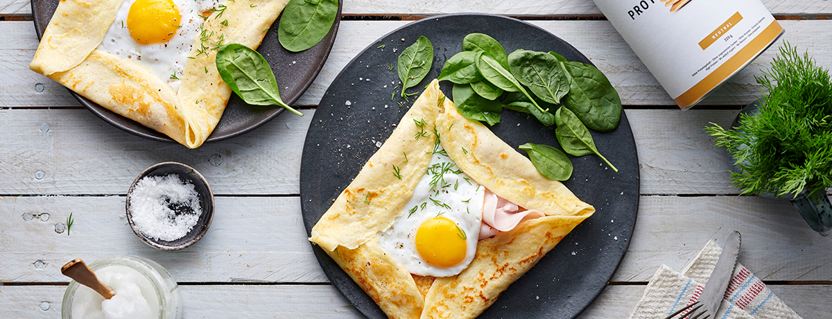 A plate of savory crepes with fried egg, with a few baby spinach leaves on the side for garnish