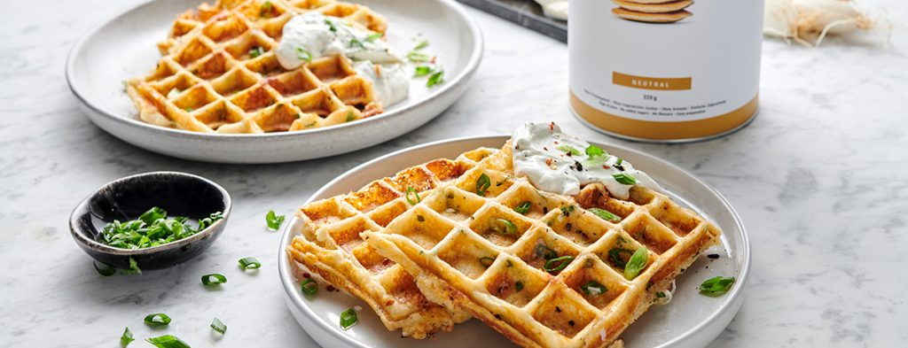 A stack of two savory waffles garnished with chives and a dollop of sour cream