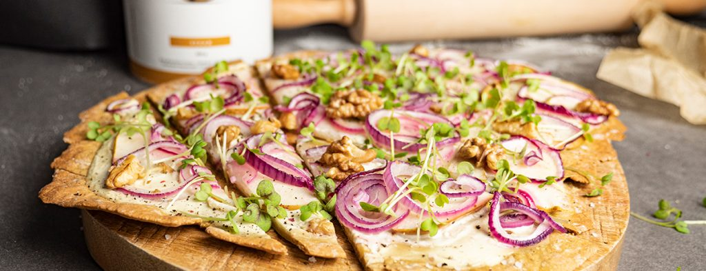 A sliced vegan protein flammkuchen topped with bright red onions, sprouts, pear and walnut halves