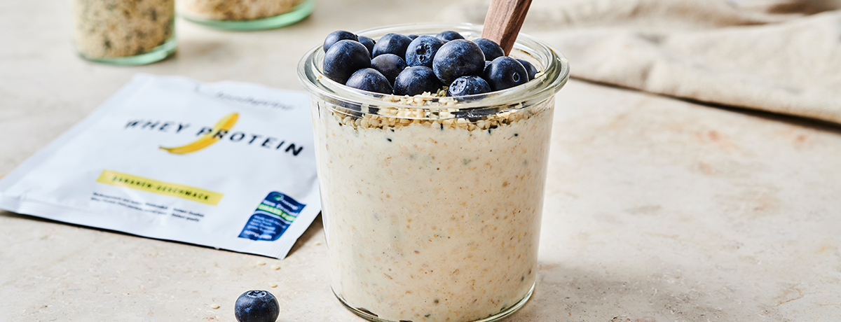 A glass jar of overnight oats topped with fresh blueberries