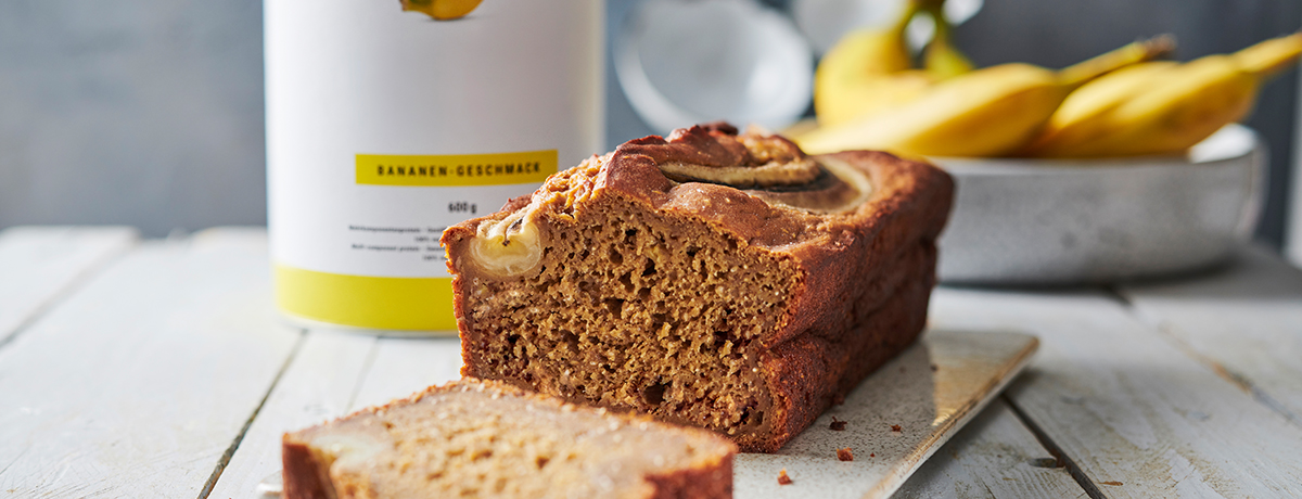 A loaf of vegan banana bread with a slice cut into it, sitting next to a canister of Vegan Protein