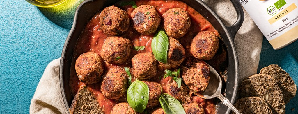 A cast-iron pan of vegan meatballs in a base of tomato sauce, garnished with a few whole basil leaves
